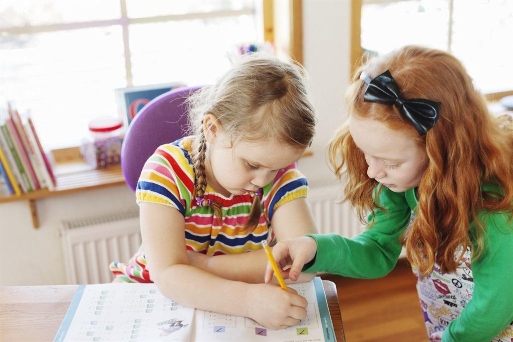 två barn sitter vid skolbänk och studerar
