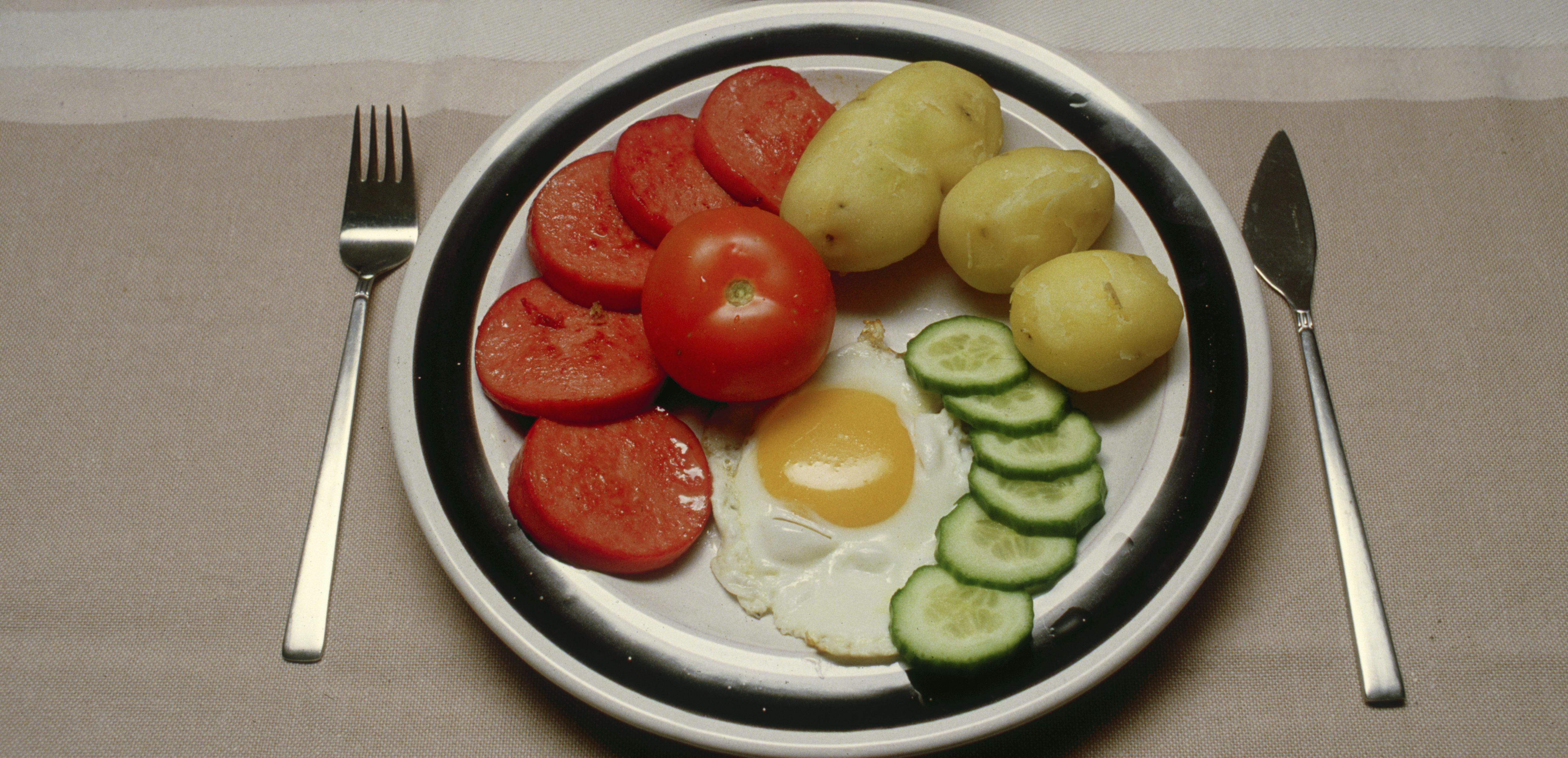 Mattallrik med stekt falukorv, stekt ägg, kokt potatis, tomat och gurka.