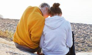 Förälder sitter med ett barn på en strand